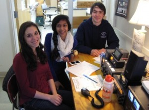 Carolyn, Teja and Ben sit around their club station.