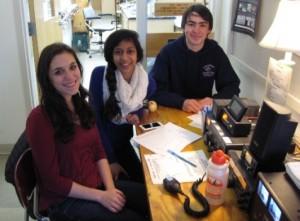 Carolyn, Teja and Ben sit around their club station.